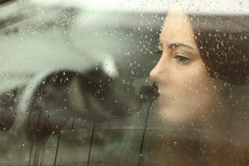 दुखी औरत खिड़की से बाहर देखती हुयी
