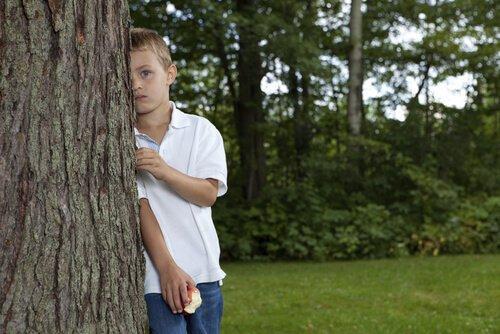 पेड़ के पीछे खड़ा बच्चा